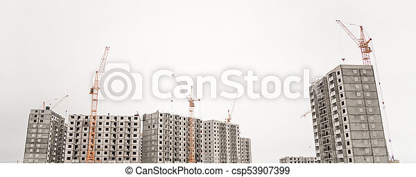 the construction crane and the building against the blue sky - csp53907399