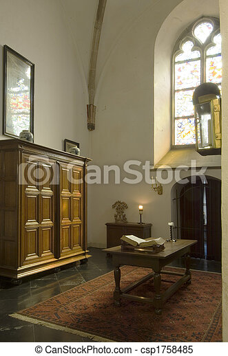 The crypt. The cript of an ancient church with the holy bible on the table,  and a burning candle in the background. light