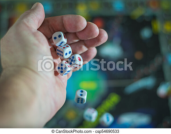 The dice fall from his hand on a colorful game Board. - csp54690533