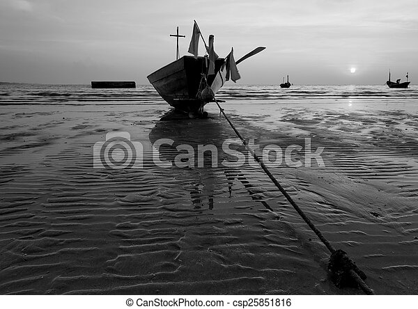 The fishing boat stuck on sand beach in black and white , Thaila