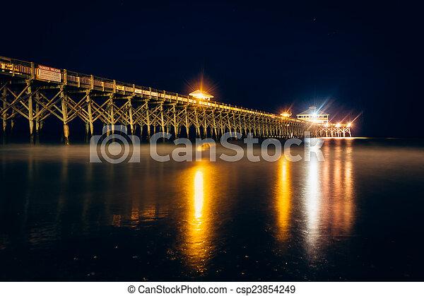 The fishing pier at night, in Folly Beach, South Carolina. - csp23854249