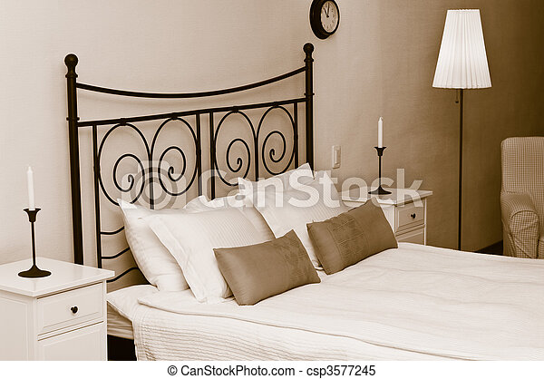 The forged headboard of bed with pillows and a white coverlet. Candles in a room interior, a bedroom - csp3577245