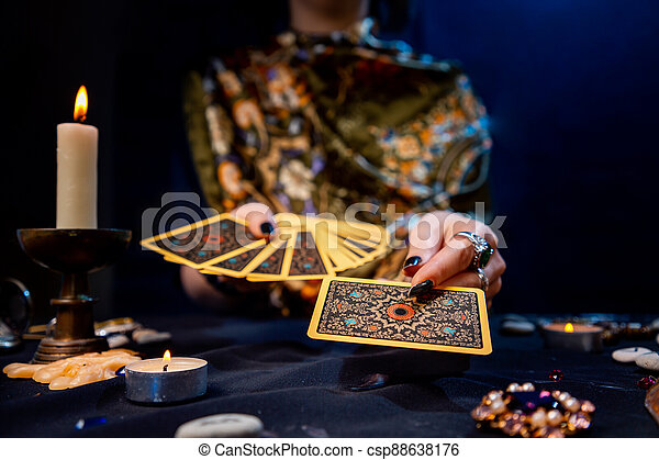 The fortune teller holds a fan of cards in her hands and holds out a card with one hand. Close-up. The concept of divination, magic and esotericism - csp88638176