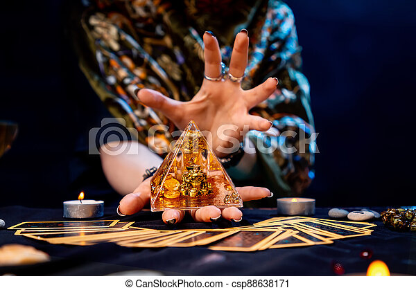 The fortune teller holds a glass pyramid with gold in her hands and casts a spell over it. There are Tarot cards on the table. Close-up. The concept of divination, magic and esotericism - csp88638171