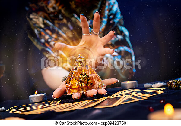 The fortune teller holds a glass pyramid with gold in her hands and casts a spell over it. Magic aura. There are Tarot cards on the table. Close-up. The concept of divination, magic and esotericism - csp89423750