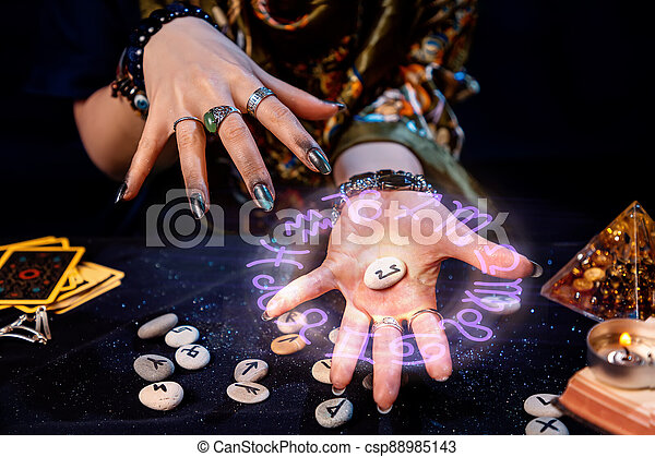 The fortune teller holds a rune with a luminous astrological circle above it in the palm of her hand. The concept of divination, astrology and predicting the future - csp88985143