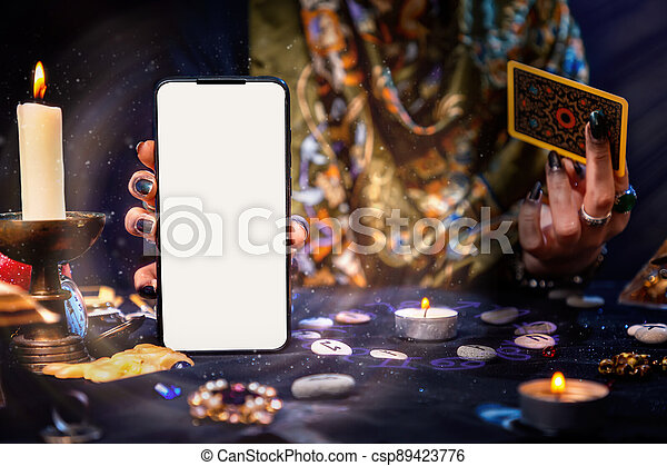 The fortune teller is holding a Tarot card and a smartphone with a white screen. Magic aura. Mock up. Close-up. The concept of divination, magic and esotericism - csp89423776