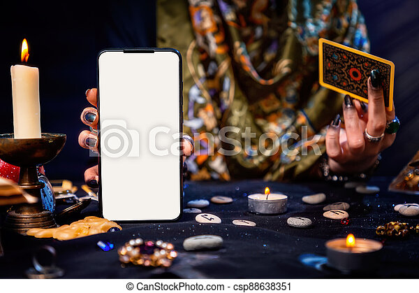The fortune teller is holding a Tarot card and a smartphone with a white screen. Mock up. Close-up. The concept of divination, magic and esotericism - csp88638351