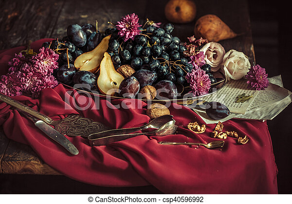 The fruit bowl with grapes and plums against a maroon tablecloth - csp40596992