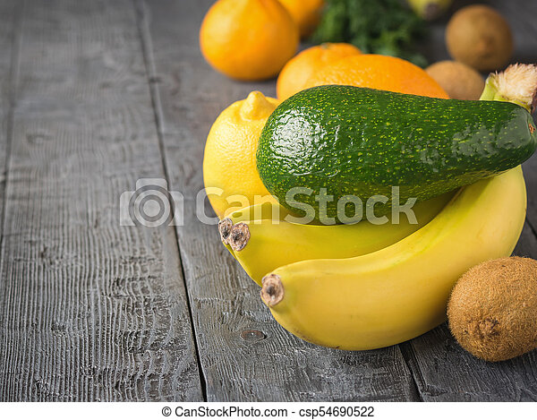 The fruit is green, ripe avocado, three bananas and other tropical fruits on a rustic table. - csp54690522