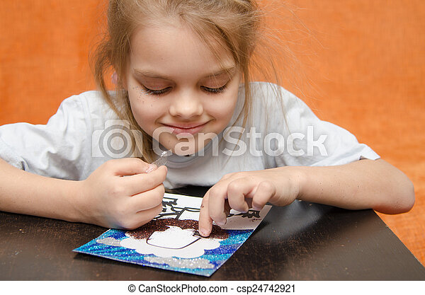 The girl at the table playing sand applique - csp24742921