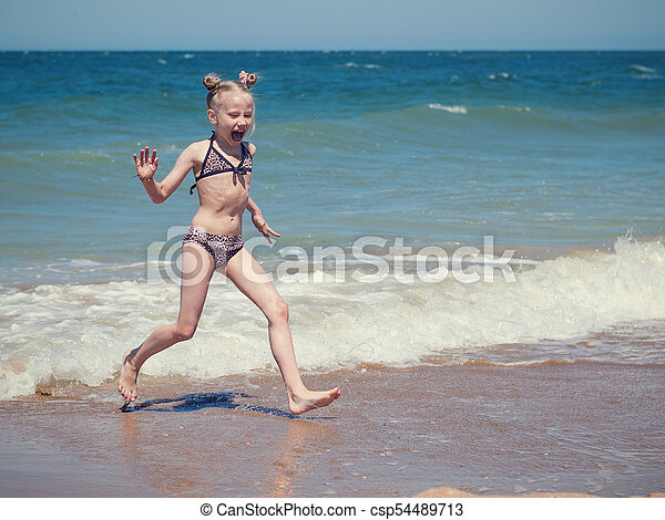 The girl runs away from a troubled sea on a summer day. - csp54489713