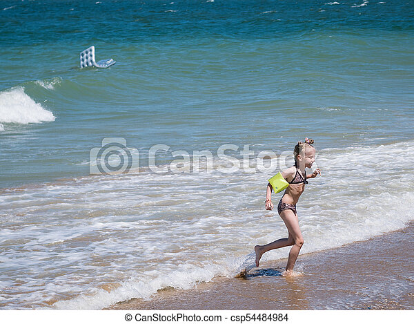 The girl runs away in fear from the raging sea. - csp54484984