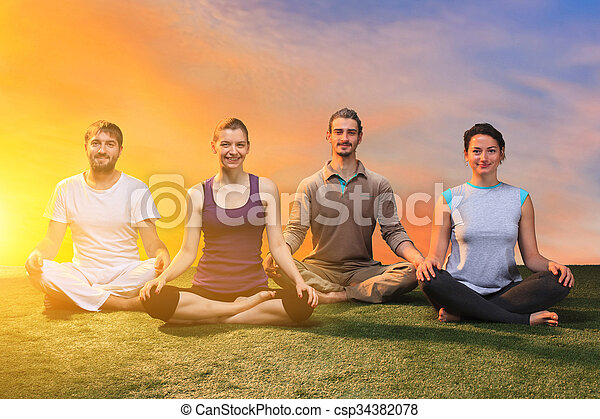 the group of people doing yoga exercises against sunset sky