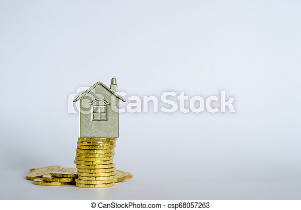The house symbol on a stack of yellow shiny coins on a light gray blue background. - csp68057263