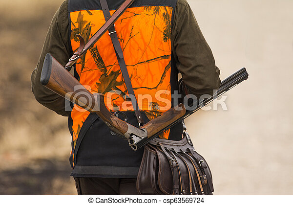 The hunter in the hunting clothes with a new hunting rifle - csp63569724