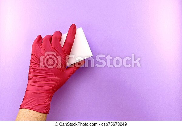 The left hand in a rubber glove, a gesture of erasing, removing something from a light purple surface, melamine sponge. - csp75673249