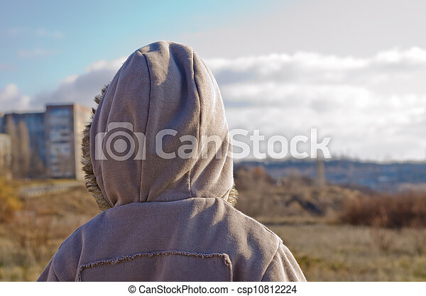 The little boy in a jacket costs a back on the nature in the autumn and looks at a city in the distance - csp10812224