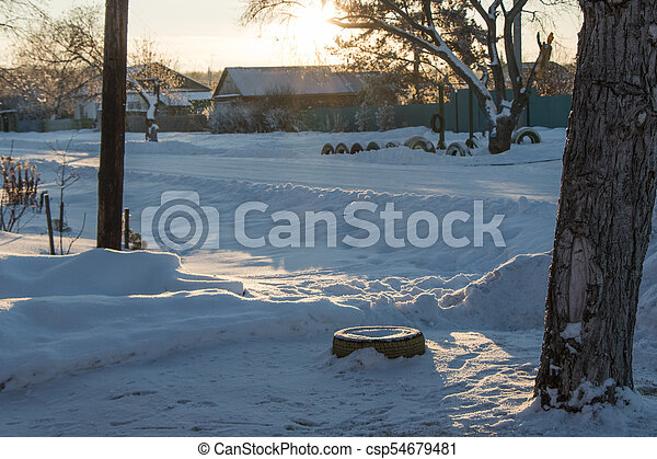 The main street of a Russian village in winter at sunset in freezing weather - csp54679481