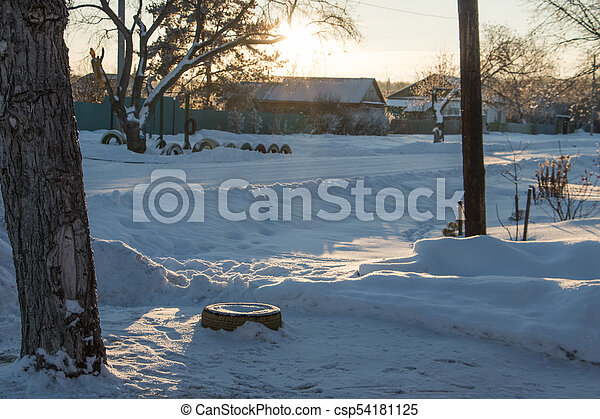 The main street of a Russian village in winter at sunset in freezing weather - csp54181125