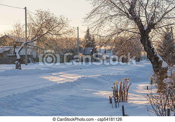 The main street of a Russian village in winter at sunset in freezing weather - csp54181126