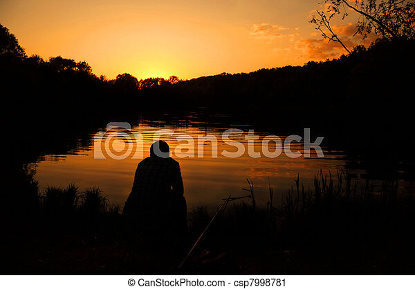 The man sits with a fishing tackle and fishes on the bank of lake, during a decline. - csp7998781