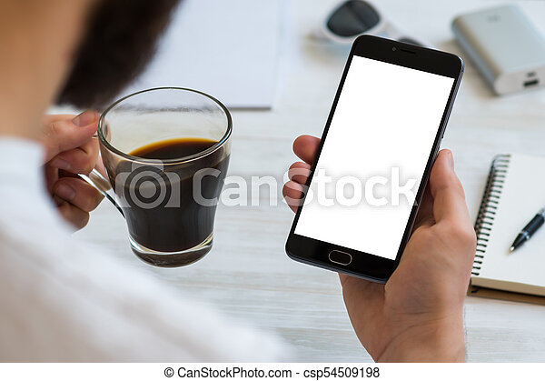 The man uses a smartphone with a white screen for the mock up Drinks coffee reading news. Concepts of using mobile devices, demos of the site in the mobile version - csp54509198