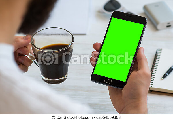 The man uses a smartphone with a with green screen for chroma key compositing Drinks coffee reading news. Concepts of using mobile devices, demos of the site in the mobile version - csp54509303