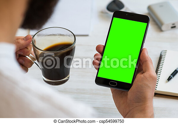 The man uses a smartphone with green screen for chroma key compositing Drinks coffee reading news. Concepts of using mobile devices, demos of the site in the mobile version - csp54599750