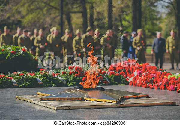 The military salutes monument to soldiers who died in World War. Victory Day Parade. Eternal Flame monument with star and flowers at Grave of Unknown Soldier - symbol of victory in Second World War - csp84288308