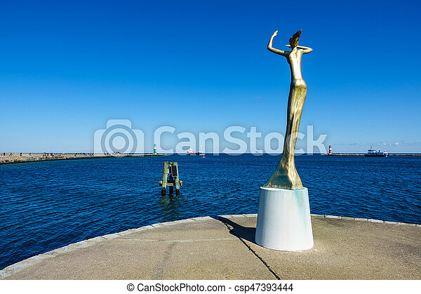 The Mole and a statue in Warnemuende, Germany - csp47393444