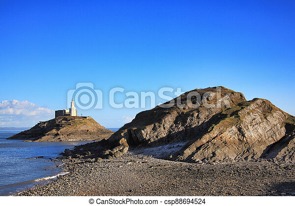 The Mumbles with it's lighthouse as seen from Bracelet Bay on the Gower Peninsular West Glamorgan Wales UK a popular Welsh coastline travel destination - csp88694524