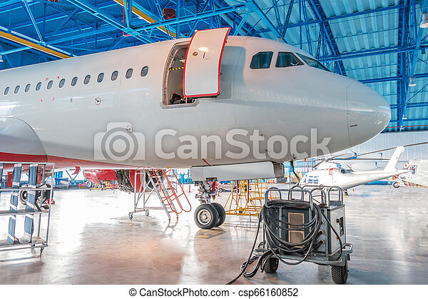 The nose of the aircraft fuselage with open door in the aircraft hangar. - csp66160852