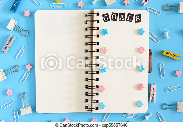 The notepad on the springs lies open. Next to the mess office supplies. The white pages of the notebook contain the inscription GOALS, pink and blue asterisks. Photo from the top on a blue background. - csp55857646