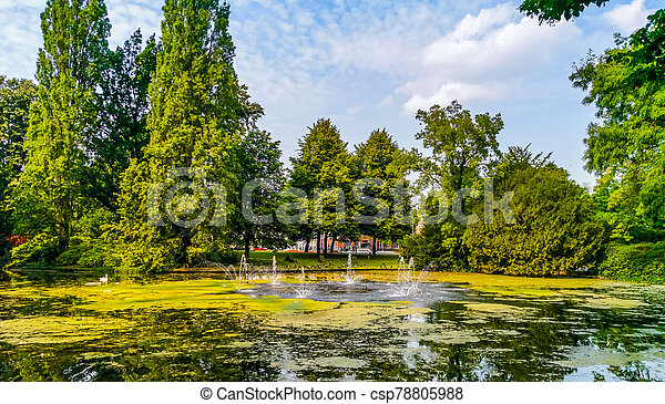 the pond with water fountains in the city park Valkenberg of breda, Nature scenery of the Netherlands - csp78805988