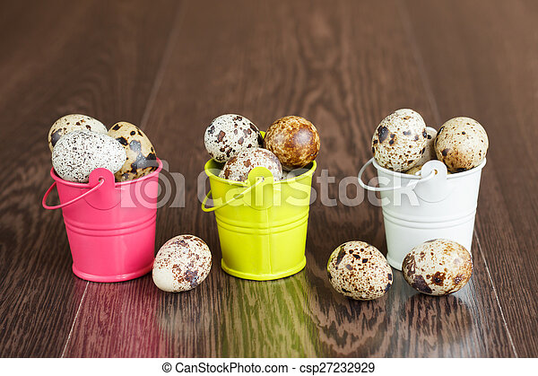 The quail eggs in a tray on a wooden table - csp27232929