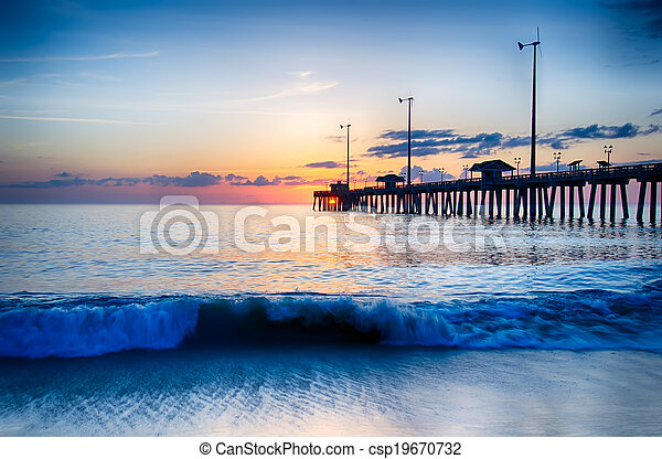 The rising sun peeks through clouds and is reflected in waves by the Nags Head fishing pier on the outer banks of North Carolina - csp19670732