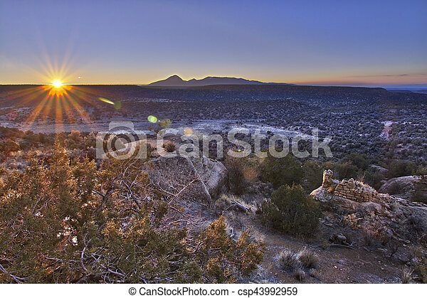 The rising sun, shining across an empty plain, lights an ancient Anasazi tower. - csp43992959