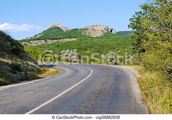 the road is rolled up against the background of high cliffs covered with grass under the blue sky - csp58862938