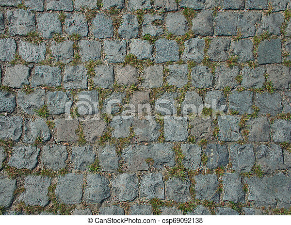 The road paved with stone sprouted grass. Texture or background. - csp69092138