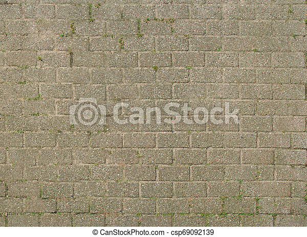 The roadway lined with stone sprouted grass. Texture or background. - csp69092139