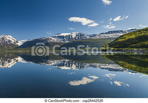 The shore of a mountain lake at sunset - csp28442526