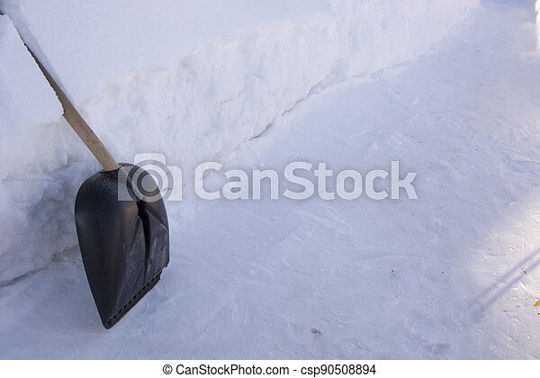 The shovel stands at a high snowdrift. Raking away the snow in the garden. There is a lot of snow in the garden in winter. - csp90508894