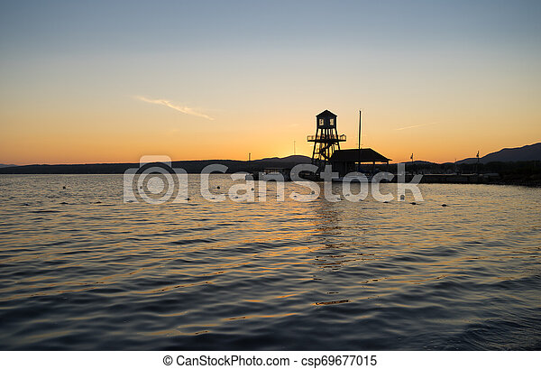 The silhouette of a lake pier and shoreline at sunset - csp69677015