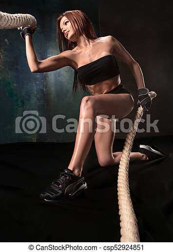 The strong young woman pulling rope at a gym - csp52924851