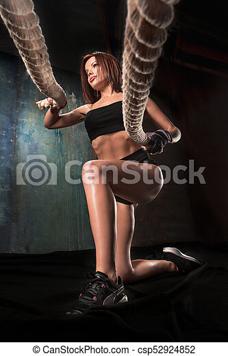The strong young woman pulling rope at a gym - csp52924852