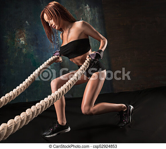 The strong young woman pulling rope at a gym - csp52924853