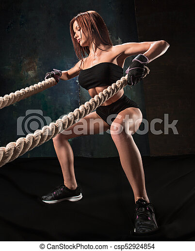 The strong young woman pulling rope at a gym - csp52924854