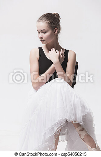 73905f1f8dec8 The teen ballerina in white pack sitting on chair - csp54056215