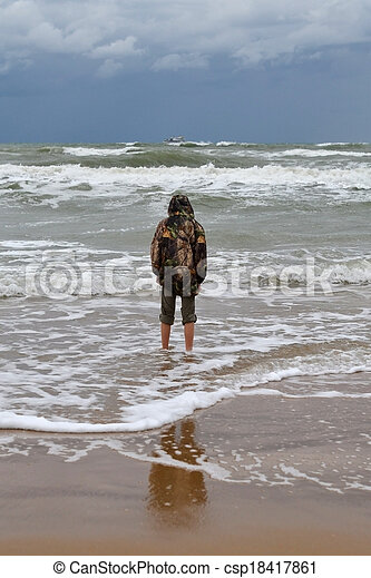 The teenager costs on the seashore in rainy weather a back in a shot - csp18417861